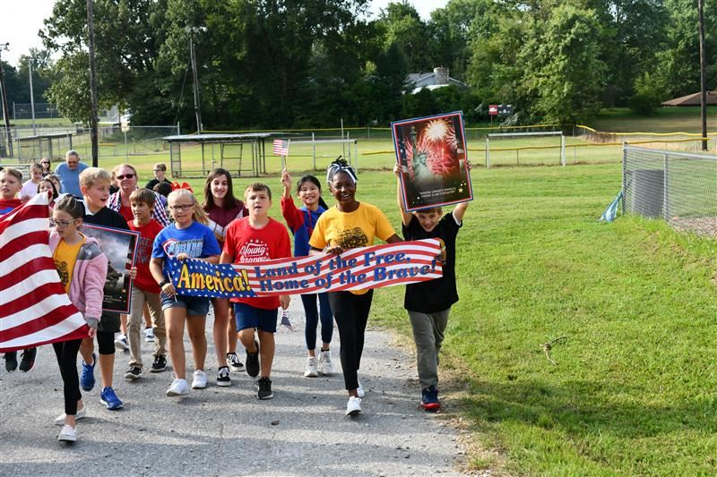 Students carry banner during Hanson Elementary Heroes Walk.