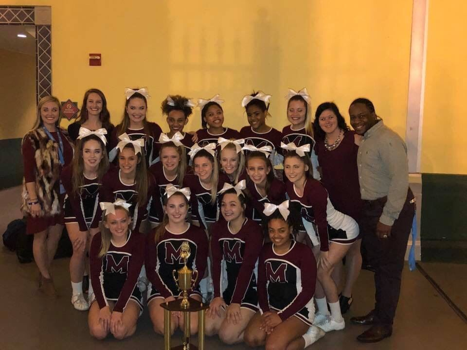Madisonville North Hopkins cheer team poses with UCA Nationals trophy.