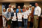 Three student finalists in the Amazing Shake hold certificates and pose with board members, administrators and educators