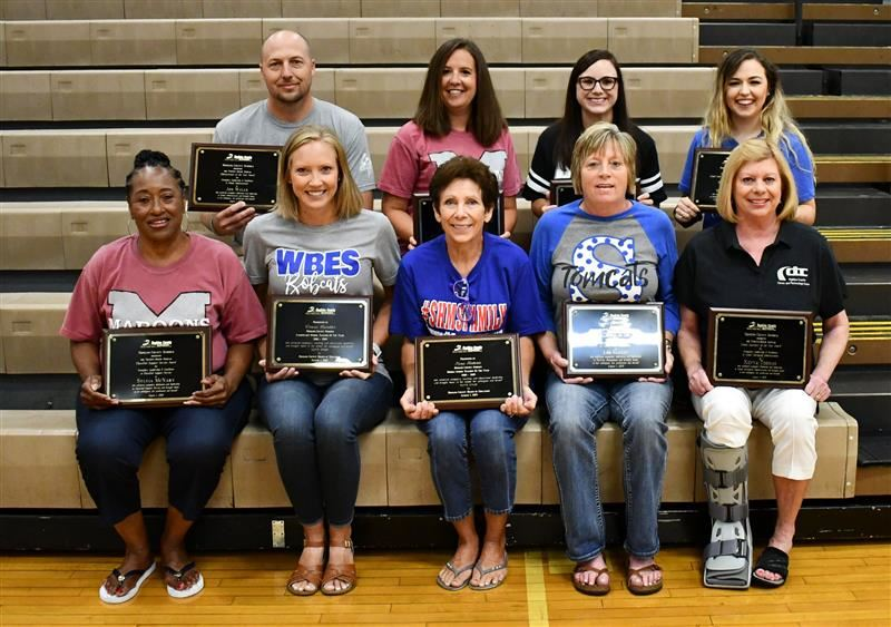 Employees of the Year winners hold their plaques while posing in school gym