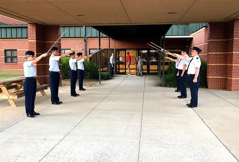 Air Force JROTC holds swords aloft in ceremony at front entrance to the school