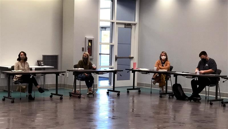 Four teachers sit at tables at the Career and Technology Center