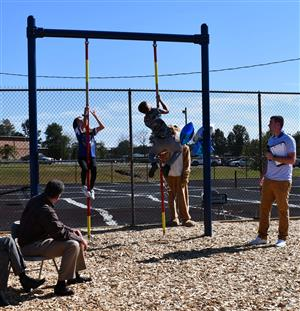 Students use rope climbing equipment.