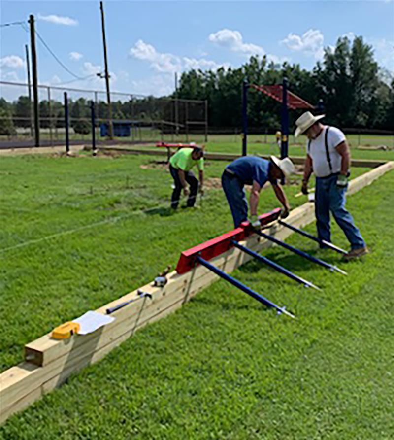 Workers install new PE equipment outside at South Hopkins MIddle School.