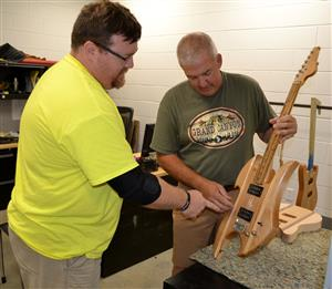 Eric Anderson displays guitar during summer workshop